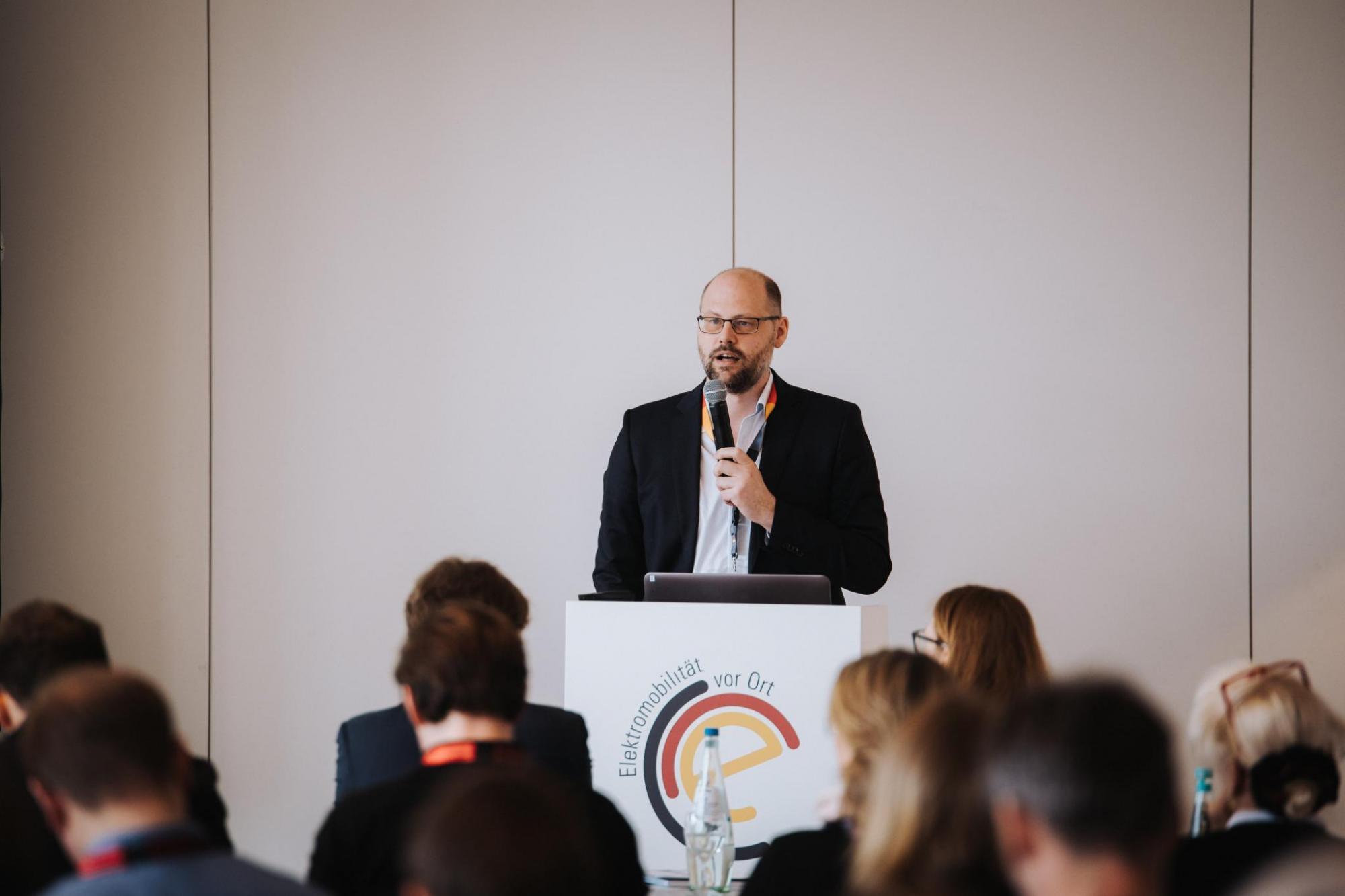 Manfred Schmid präsentiert die Broschüre zur Elektromobilität in kommunalen Mobilitätsstrategien